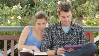 University students study on campus outdoors with book and tablet for exams