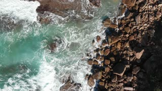 Aerial coastal top view of waves breaking on rocks - Slow motion
