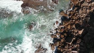 Aerial coastal top view of waves breaking on rocks - Slow motion