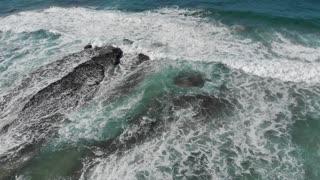 Aerial coastal top view of waves breaking on rocks