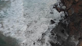Aerial coastal top view of waves breaking on rocks