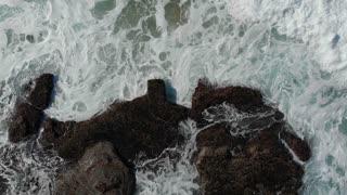 Aerial drone footage top view of seashore ocean waves crashing on rocky coastlin