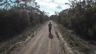 Aerial footage riding e-Bike pedal-assisted electric mountain bike dirt trail