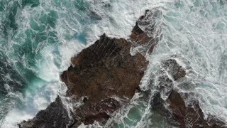 Aerial of the ocean waves washing up on rocks - Slow motion