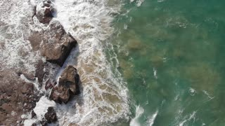 Aerial view of ocean waves crashing on rocky coastline