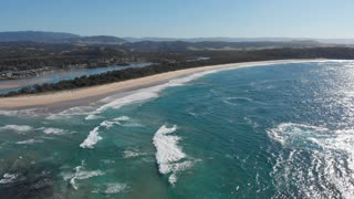 Australia aerial ocean waves breaking on sandy beach