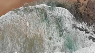 Beach aerial drone footage ocean waves breaking coast seashore