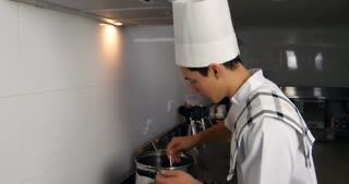 Chef tasting food cooking on stove in gourmet restaurant kitchen