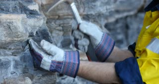 Close up of Geologist hand taking rock sample with pick axe mining exploration