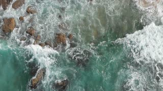 Coastline view and waves crashing on rocky cliff shoreline - Slow motion