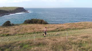 Cross-country runner jogging with dog along coastal track