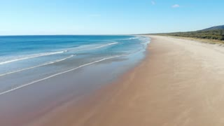 Deserted sandy beach Australia aerial ocean waves breaking on beach