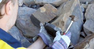 Geologist braking coal sample with pick axe mining exploration