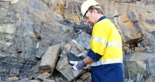 Geologist engineer man examines coal sedimentary layer for mining industry