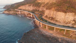 Grand Pacific drive's Sea Cliff Bridge morning aerial footage NSW Australia