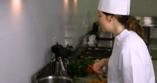 Happy young chef smelling food cooking in gourmet restaurant kitchen
