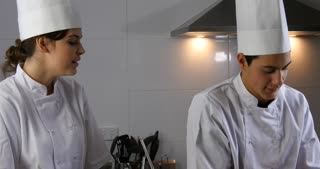 Happy young chefs smelling food cooking in gourmet restaurant kitchen