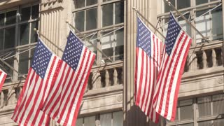 Iconic New York City building with American flag in slow motion