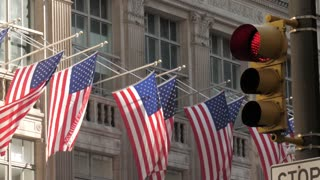 Iconic shot of New York city with American flag, buildings traffic light
