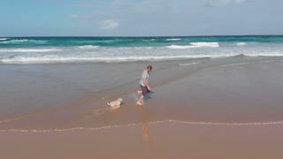 Man running on beach with dog through water - Slow motion