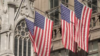 New York city cutaway of American flags on building iconic shot