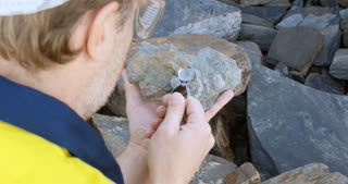 Paleontologist working in the field of paleontology looking at fossil