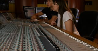 People working audio studio recording desk equipment in music recording studio