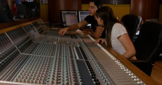 Recording studio music mixing desk console with engineer teaching student