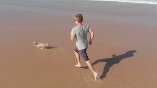 Running with dog on beach slow motion feet splashing water seascape