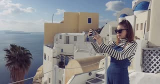 Santorini Greece - Girl taking photos village of Oia in Aegean