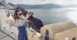 Santorini Greece - Tourist girl taking selfie village of Oia in Aegean