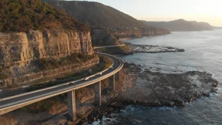 Sea cliff bridge drive coastal landscape Australia aerial footage sunrise