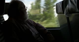 Senior retired man on train looking out window while on vacation
