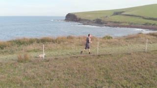 Slow-mo cross-country runner jogging with dog along coastal track