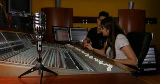 Smiling to camera while working on studio recording in music recording studio
