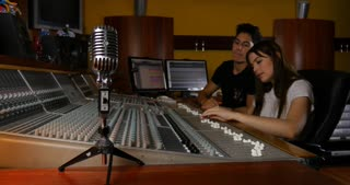 Students smiling while working on studio recording in music recording studio