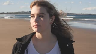 Wind in hair young attractive woman outdoors walking on sandy beach