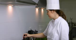Young female chef tasting food cooking smiling to camera