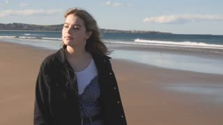 Young woman in late teens walking alone on deserted beach