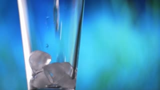 Water pouring into glass with ice slow motion fresh natural cool with bubbles.