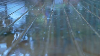 Wet Weather Rain Drops Splash on reflective Wood Surface in slow motion