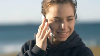 Woman talking on phone smiling looking happy outdoors