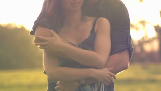 Young couple in loving relationship hugging outdoors lifestyle