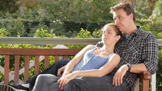 Young couple sitting in park cuddeling on park bench showing afection
