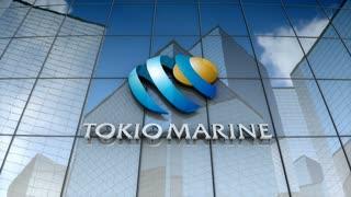 Editorial, Tokio Marine Holdings, Inc. logo on glass building.