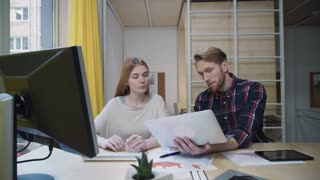 A bearded man with a laptop showing the employee data that she enters into your computer.