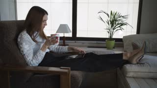A businesswoman is relaxing in the comfort zone. She uses the tablet for surfing the Internet and happy with it
