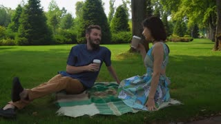 A guy with a beard with a girl in dress sitting on a park lawn on blankets on the floor and drinking coffee from plastic cups