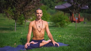 A man in dark pants on green grass in a sunny park yoga