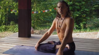 A man who performs yoga exercise twisting, touching his hand to foot